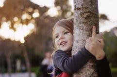 Sonrisa hermosa de la niña, abrazando un tronco de árbol Pequeña bailarina fotografía de archivo libre de regalías