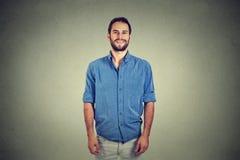 Sonrisa hermosa del hombre joven aislada contra fondo gris de la pared fotografía de archivo
