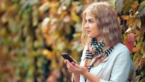Sonrisa hermosa feliz de la mujer y usar su teléfono en parque del otoño almacen de video