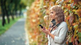 Sonrisa hermosa feliz de la mujer y usar su teléfono en parque del otoño metrajes