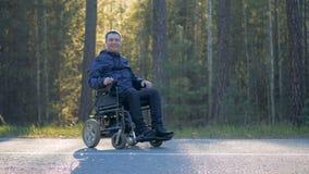 Sonrisa hombre físicamente desafiado que se sienta en una silla de ruedas accionada al aire libre almacen de metraje de vídeo