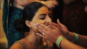 Sonrisa india de la novia mientras que la mujer cubre su cara con curcumina metrajes