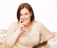 Sonrisa interior gorda bastante grande de la mujer de los jóvenes en casa, gesticulando Fotos de archivo libres de regalías