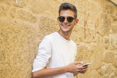 Sonrisa joven con el teléfono móvil en la ciudad Fotografía de archivo
