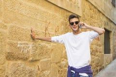 Sonrisa joven con el teléfono móvil en la ciudad Fotografía de archivo libre de regalías