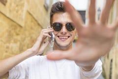 Sonrisa joven con el teléfono móvil en la ciudad Imagen de archivo