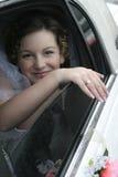 Sonrisa joven de la novia en una limusina Foto de archivo libre de regalías