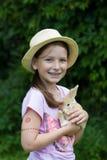 Sonrisa linda de la muchacha, celebrando un pequeño conejito beige Fotos de archivo