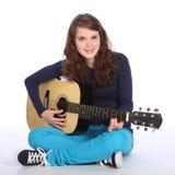 Sonrisa linda de la muchacha del adolescente en la guitarra acústica Fotos de archivo libres de regalías