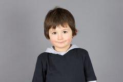 Sonrisa linda del niño pequeño sobre gris Fotos de archivo