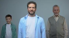 Sonrisa masculina de mediana edad en la cámara, el hombre y el muchacho detrás, último mayor y futuro metrajes