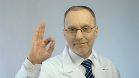 Sonrisa masculina del médico, mostrando el gesto ACEPTABLE, seguro de resultados de tratamiento acertados almacen de video