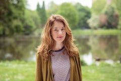 Sonrisa muchacha adolescente bastante rubia en la orilla del lago Fotos de archivo libres de regalías
