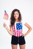 Sonrisa muchacha bastante adolescente que sostiene la bandera de los E.E.U.U. Imagen de archivo