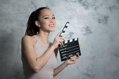 Sonrisa mujer bastante adolescente que usa la chapaleta de la película Imagen de archivo libre de regalías