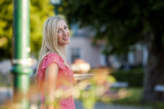 Sonrisa mujer bastante rubia que se coloca en lado del camino Fotografía de archivo