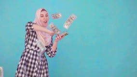 Sonrisa musulmán joven de la mujer y dinero que lanza que miran la cámara almacen de metraje de vídeo