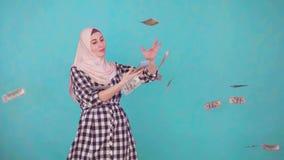 Sonrisa musulm?n joven de la mujer y dinero que lanza que miran la c?mara almacen de metraje de vídeo