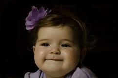 Sonrisa púrpura de la muchacha de flor Imágenes de archivo libres de regalías