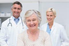 Sonrisa paciente mayor con los doctores en clínica Fotos de archivo