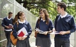 Sonrisa que habla que camina de los estudiantes junto imagenes de archivo