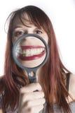 Sonrisa que magnifica de la mujer joven con la lupa Imágenes de archivo libres de regalías