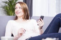 Sonrisa que se sienta de la muchacha cabelluda marrón feliz en un sofá Foto de archivo