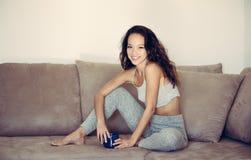 Sonrisa relajada en la mujer adolescente del sofá que se sienta con la taza Imagenes de archivo