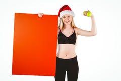 Sonrisa rubia del ajuste festivo en la cámara que sostiene el cartel Fotografía de archivo libre de regalías