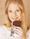 Sonrisa rubia del chocolate de la consumición del adolescente de la belleza joven Foto de archivo libre de regalías