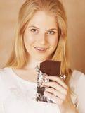 Sonrisa rubia del chocolate de la consumición del adolescente de la belleza joven Imagenes de archivo