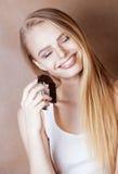 Sonrisa rubia del chocolate de la consumición del adolescente de la belleza joven Imagen de archivo libre de regalías