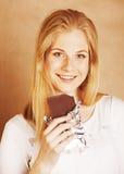 Sonrisa rubia del chocolate de la consumición del adolescente de la belleza joven Fotos de archivo