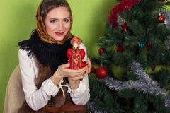 Sonrisa soñando a la mujer en mantón con sostener el regalo rojo en Nochevieja fotografía de archivo libre de regalías