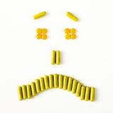 Sonrisa triste y gritadora hecha de muchas cápsulas de las píldoras Concepto de la salud Fotos de archivo