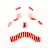 Sonrisa triste y gritadora hecha de muchas cápsulas de las píldoras Concepto de la salud Foto de archivo