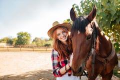 Sonrisa vaquera de la mujer bastante joven en sombrero con su caballo Foto de archivo libre de regalías