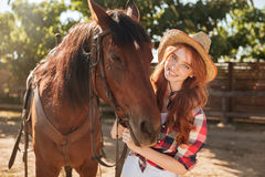 Sonrisa vaquera de la mujer bastante joven en sombrero con su caballo Imagen de archivo libre de regalías