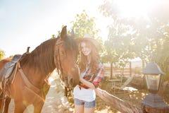 Sonrisa vaquera de la mujer bastante joven en sombrero con su caballo Imágenes de archivo libres de regalías