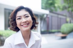 Sonrisa y mirada asiáticas felices de la muchacha en la cámara en al aire libre del condomin Imagen de archivo