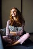 Sonrisa y miradas hermosas de la muchacha hacia fuera la ventana con una almohada en su mano Fotografía de archivo