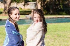 Sonrisas adolescentes de las toallas de la piscina de la nadada de las muchachas Foto de archivo libre de regalías
