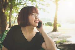 Sonrisas asiáticas lindas de la mujer y el hablar en el teléfono móvil mientras que se sienta en día de primavera del parque imagen de archivo