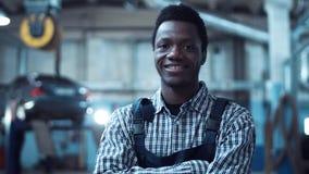 Sonrisas de la camisa rayada del mecánico de automóviles que llevan Fotografía de archivo