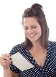 Sonrisas de la mujer mientras que lee una nota Imagenes de archivo