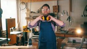 Sonrisas de trabajo del carpintero en la cámara, colocándose en un taller Funcionamiento mayor del carpintero almacen de video