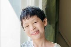 Sonrisas del muchacho y mirada de la cámara Imágenes de archivo libres de regalías