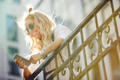 Sonrisas felices y comunicación de la mujer joven sobre el teléfono en la calle imagenes de archivo