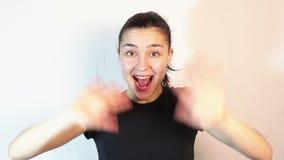 Sonrisas hermosas jovenes de la muchacha ampliamente y agitando sus brazos en el saludo almacen de metraje de vídeo