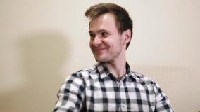 Sonrisas jovenes del hombre de negocios que se sientan en su oficina metrajes